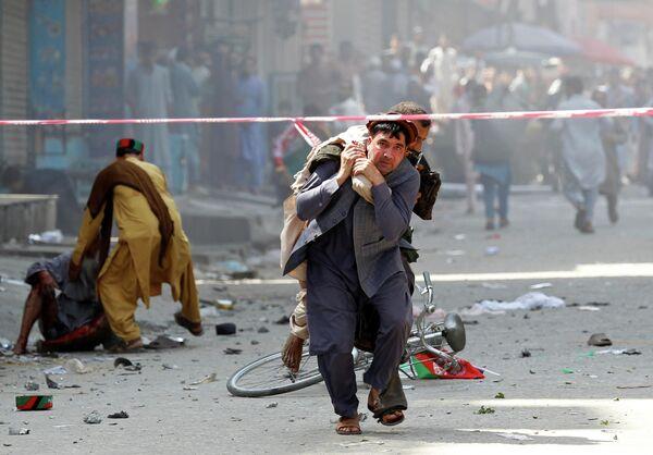 Мужчина несет раненого в госпиталь в Джелалабаде, Афганистан
