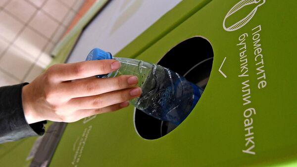 Девушка сдает пластиковую бутылку в фандомат по сбору пластиковой и алюминиевой тары