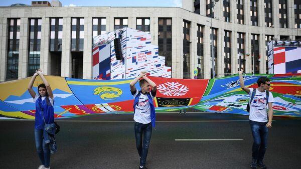 Участники флешмоба в честь Дня государственного флага России развернули на проспекте Сахарова в Москве полотно, состоящее из 2 тысяч флагов российских городов и общественных организаций