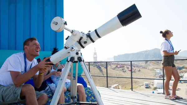 Зрители наблюдают через любительский телескоп за показательными выступлениями авиации в небе над площадкой фестиваля творческих сообществ Таврида-АРТ в бухте Капсель в Судаке