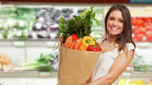 Девушка покупает овощи в магазине