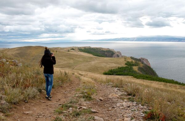 Девушка фотографирует пейзаж на острове Ольхон в Иркутской области