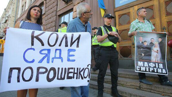 Участники акции против экс-президента Украины Петра Порошенко стоят с плакатами у здания Государственного бюро расследований
