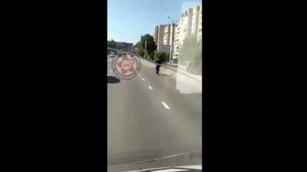 Мужчина в форме священника передвигается на самокате по автомобильной дороге в черте города Смоленск