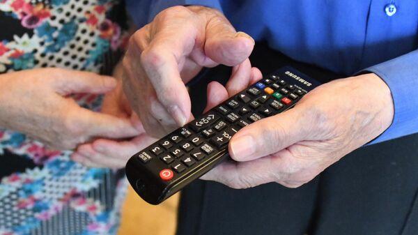 Телевизионный пульт в руке телезрителя
