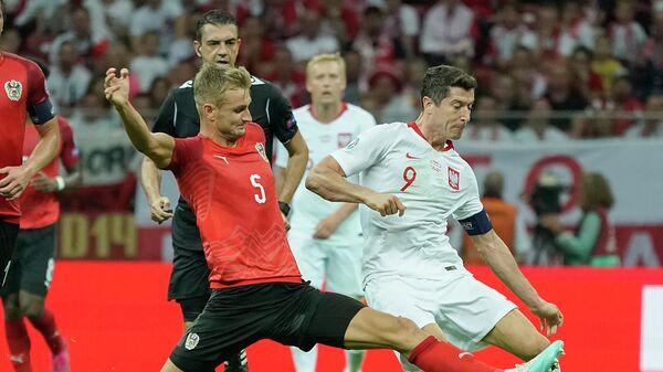 Нападающий сборной Польши Роберт Левандовский (справа) и защитник сборной Австрии Штефан Пош