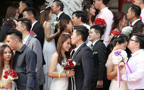 Молодожены целуются во время массовой свадебной церемонии в Куала-Лумпуре, Малайзия