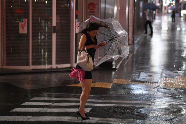 Женщина держит зонтик во время сильного ветра в Токио