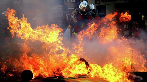 Пожарные тушат баррикаду во время акции протеста, призывающей власти принять экстренные меры против изменения климата, в Париже. 21 сентября 2019