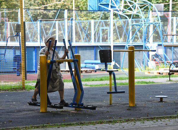 Пожилая женщина занимается на благоустроенной спортивной площадке около улицы Удальцова в Москве