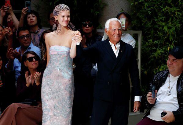 Итальянский дизайнер Джорджо Армани с моделью во время Недели моды в Милане