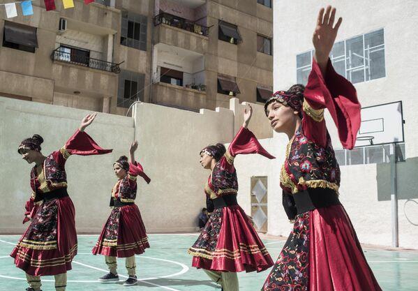Выступление девушек в национальных костюмах на открытии школы в районе Барза в Дамаске, отремонтированной на собранные в России средства
