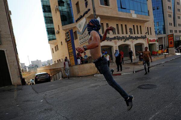 Демонстрант кидает камни в израильские войска во время акции солидарности с палестинскими заключенными, которые находятся в тюрьмах Израиля
