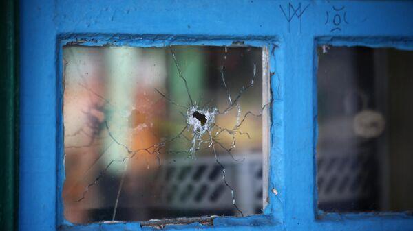 Окно жилого дома, разбитое осколком снаряда, в Донбассе