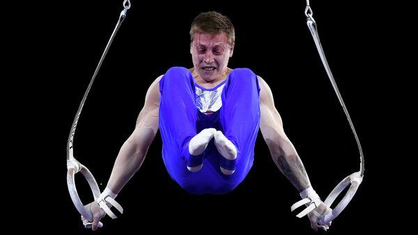Денис Аблязин (Россия) выполняет упражнения на кольцах в командном многоборье среди мужчин на чемпионате мира по спортивной гимнастике в Штутгарте.