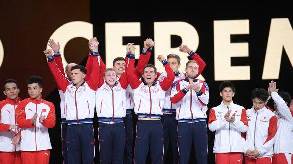 Спортсмены сборной России (в центре), завоевавшие золотые медали в командном многоборье среди мужчин, на церемонии награждения на чемпионате мира по спортивной гимнастике в Штутгарте.