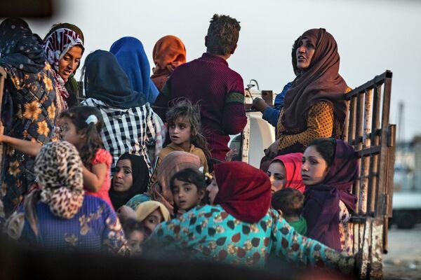 Жители уезжают из-за турецкой бомбардировки северо-восточного города Сирии Рас-эль-Айн в провинции Хасаке вдоль границы с Турцией