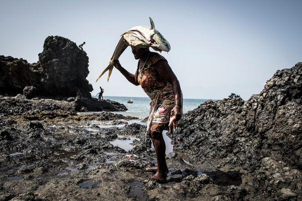 Женщина несет на голове рыбу в рыбацкой деревушке Porto Mosquito в Сантьяго