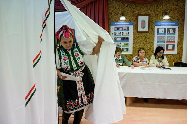 Женщина в традиционной одежде выходит из кабины для голосования, Венгрия.