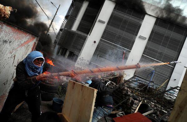 Демонстрант стреляет из самодельного оружия во время акции протеста в Кито, Эквадор