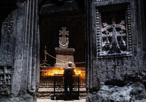Верующий в монастыре Гегард в Котайкской области Армении