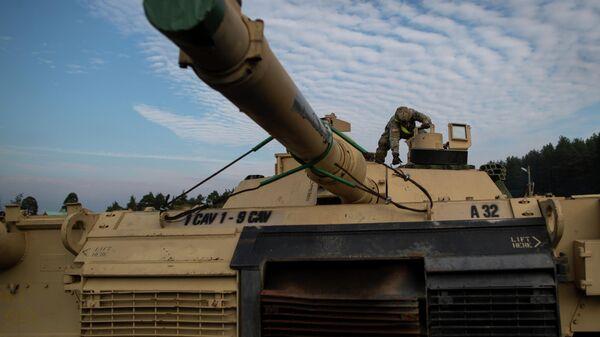 Американский военнослужащий готовит танк Abrams к разгрузке на железнодорожной станции в Литве