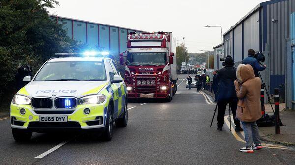 Полиция сопровождает грузовик, в котором были обнаружены телами, в британском городе Грейс