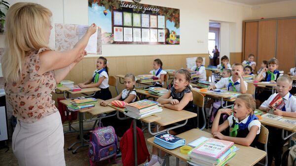 Учитель ведет урок у учеников начальной школы