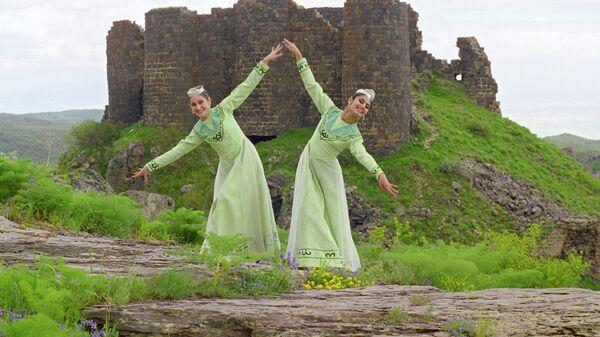 Танец у стен крепости Амберд - исторического комплекса, из замка и церкви, на склоне горы Арагац в Армении