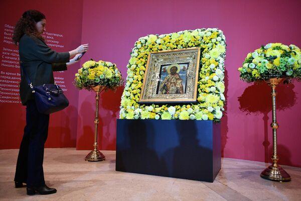 Посетительница фотографирует икону Святителя Николая Чудотворца на выставке Память поколений: Великая Отечественная война в изобразительном искусстве