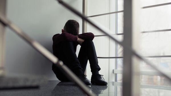 Грустный мальчик сидит на лестнице