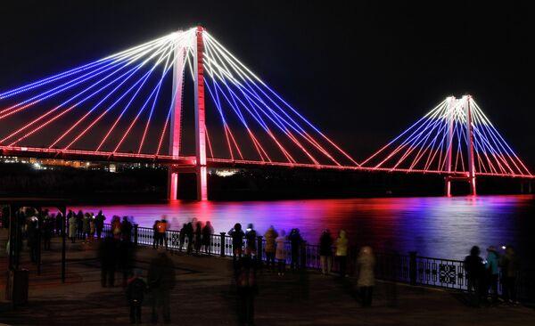 Зрители смотрят на окрашенный в цвета российского государственного флага Виноградовский пешеходный мост в Красноярске
