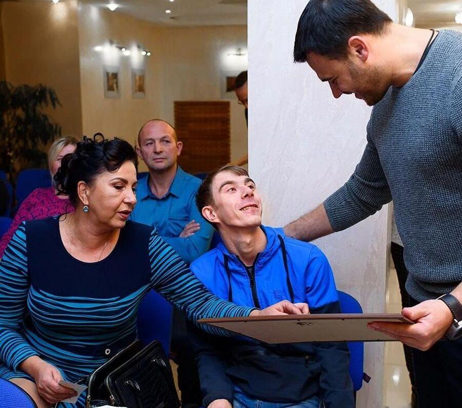 Влад дарит свою картину певцу Эмину Агаларову, который помог оплатить ему один из курсов реабилитации за границей