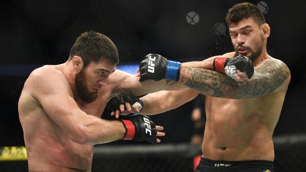 Шамиль Гамзатов (Россия) и Клидсоном Абреу (Бразилия) (справа) во время боя в полутяжелом весе на турнире по смешанным единоборствам UFC Fight Night в Москве.