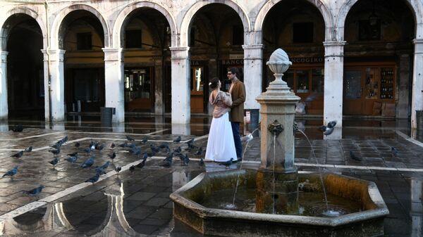 Молодые люди у фонтана на одной из улиц в Венеции