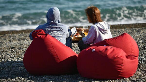Молодые люди обедают на берегу моря