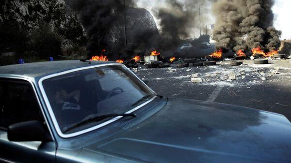 Мужчина спит в машине рядом с горящими шинами, Ливан, 13 ноября 2019 года