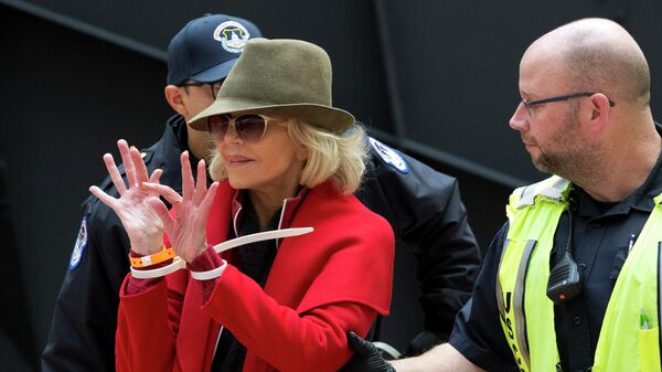 Джейн Фонда во время ареста полицией во время экологической акции у здания Капитолия, США