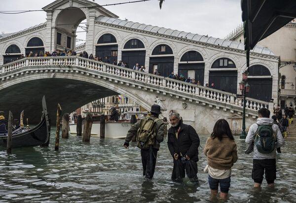 Прохожие у моста Риальто в Венеции во время наводнения