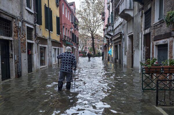 Прохожий на одной из улиц в Венеции во время наводнения