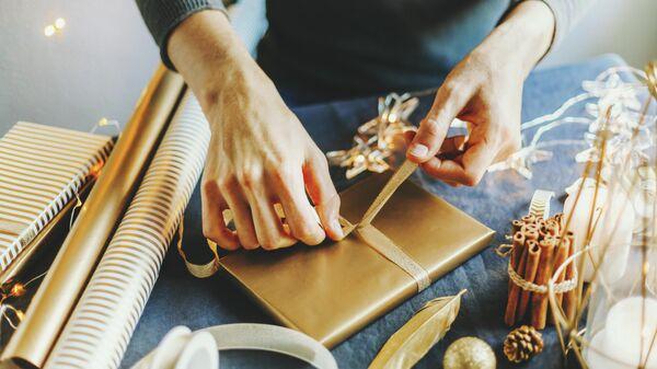 Мужчина упаковывает подарок