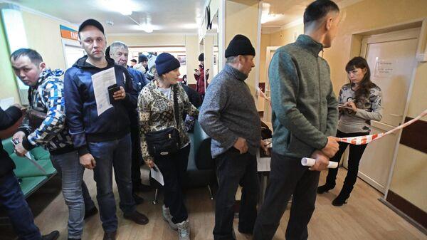 Люди стоят в очереди в наркологическом диспансере