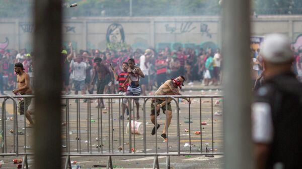 Болельщики ФК Фламенго забрасывают полицейских бутылками, камнями и пиротехникой во время Чемпионского парада