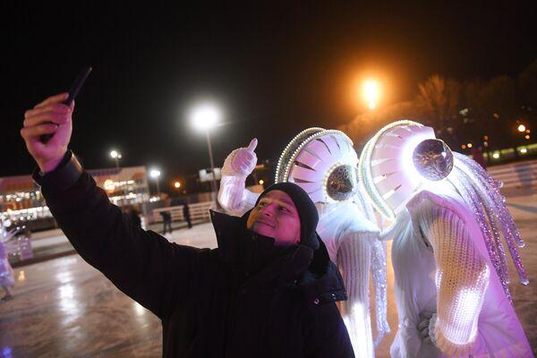 Молодой человек фотографируется с аниматорами на открытии катка Восход в Центральном парке культуры и отдыха имени Горького в Москве