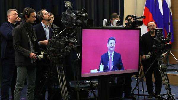 Журналисты у монитора с изображением председателя КНР Си Цзиньпина