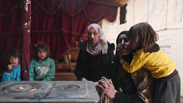 Женщины с детьми, живущие в палаточном городке при частном заводе по разбору, сортировке, выплавке и прессовке алюминиевого лома в южном пригороде Дамаска