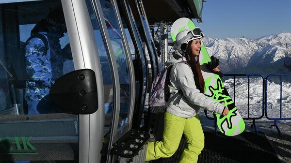 Отдыхающие выходят из кабинки канатной дороги на горнолыжном склоне во время открытия сезона на горном курорте Горки Город на территории Красной Поляны