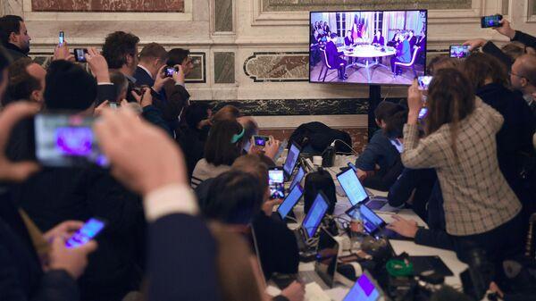 Журналисты смотрят трансляцию встречи глав государств-участников Нормандского формата в Елисейском дворце