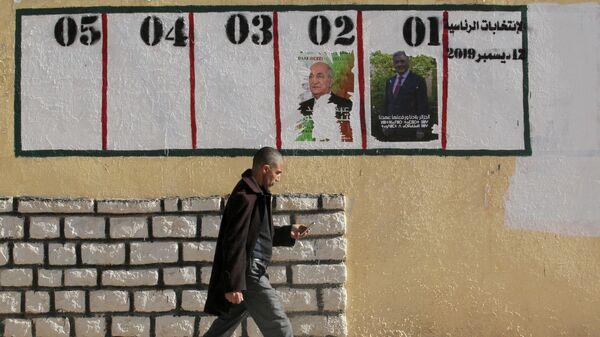 Мужчина проходит мимо предвыборных плакатов в Айн-Усера, Алжир