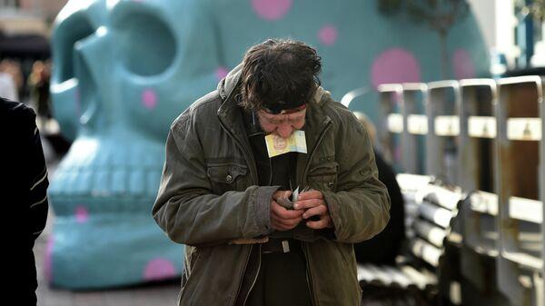 Мужчина считает деньги возле уличного кафе в центре Киева, Украина